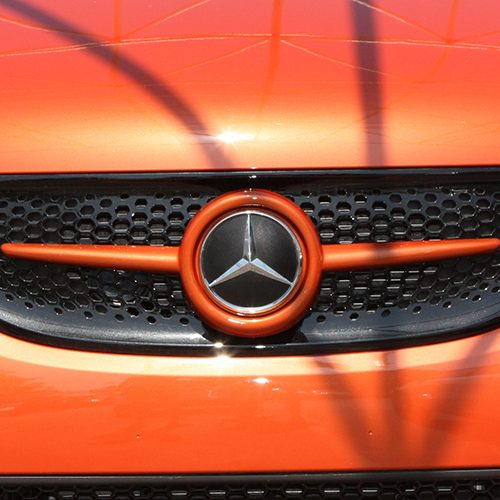 This is the Front Grille for Smart Fortwo 45. Its color is Lava Orange Metallic and it has Mercedes Emblem.