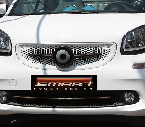 This is the new Smart Fortwo 453, in white color. Its front end is customized with Smart Power Design's Carbon accessories. The Front Grille and the Low Grill Trim Strip Piece, both in carbon finish, have been installed on it.