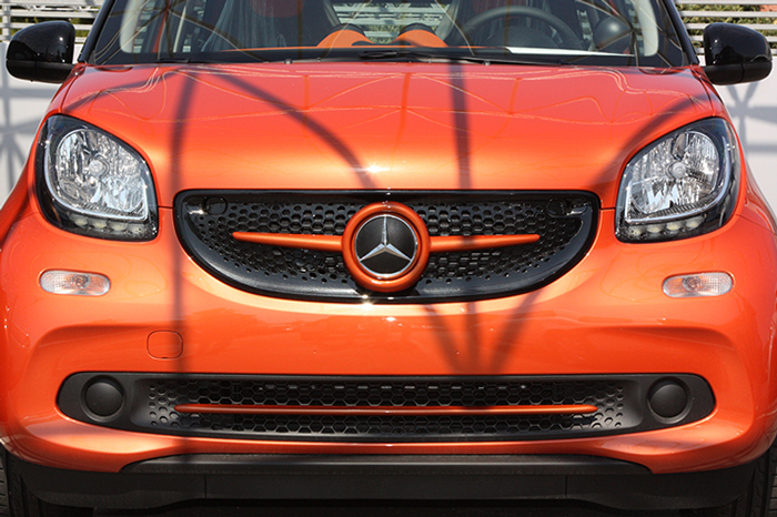 This is the new Smart Fortwo 453, in Lava Orange Metallic color, tuned with Smart Power Design's accessories. The Front Grille and the Low Grill Trim Piece have been installed.