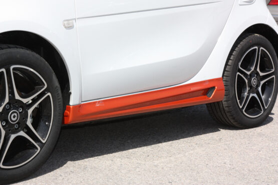 These are the Side Skirts for the Smart Fortwo 453, in Lava Orange Metallic color, brought to you by Smart Power Design. The Fender Flares are also installed.