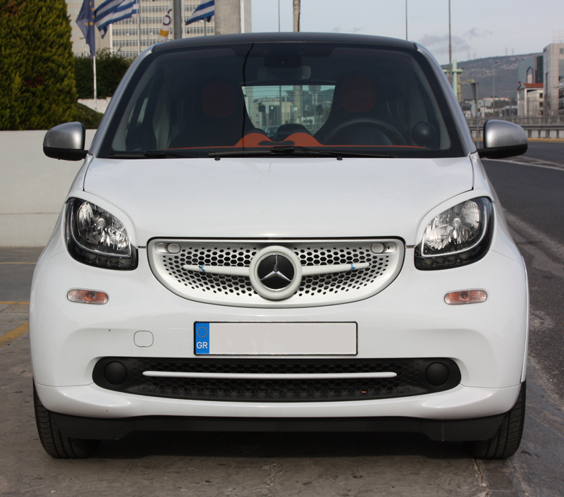 This is a white Smart Fortwo 453 with its front end tuned by Smart Power Design. It has installed the Front Grille, the Low Grill Trim piece and the Headlight Eyebrows.