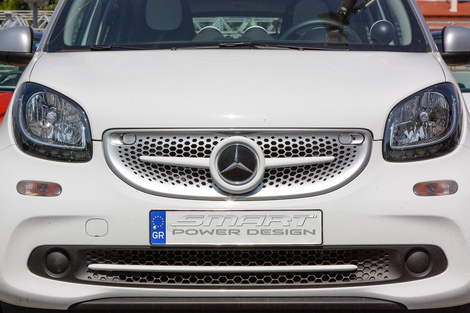 This is a close up photo of a white Front Grille installed on a Smart Fortwo 453.
